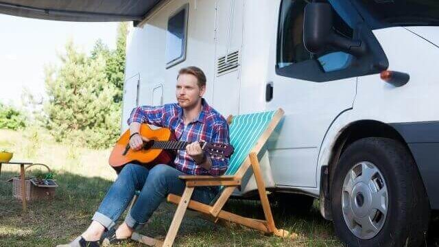 ギターを弾きながら待つ男性