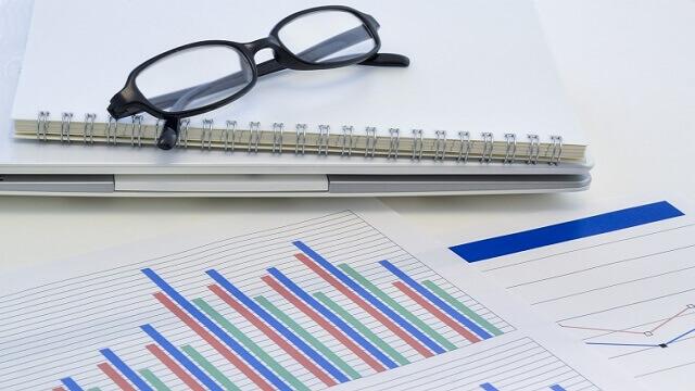 データをまとめた書類とノートと眼鏡