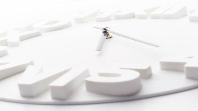 1日の時間を刻む白い文字盤の時計