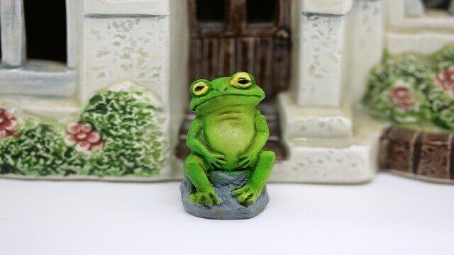空腹でお腹を押さえて座り込む蛙の置物
