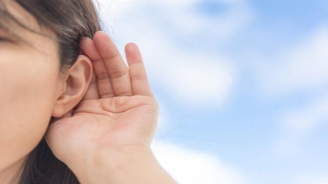 耳に手を当て話を聞いている女性