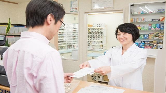 薬局の受付をする薬剤師と患者